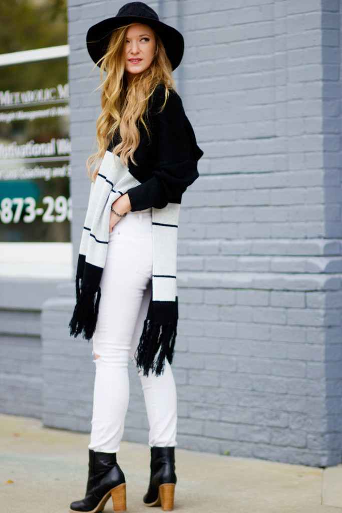 black and white poncho, white dressed jeans, and black chunky heel booties