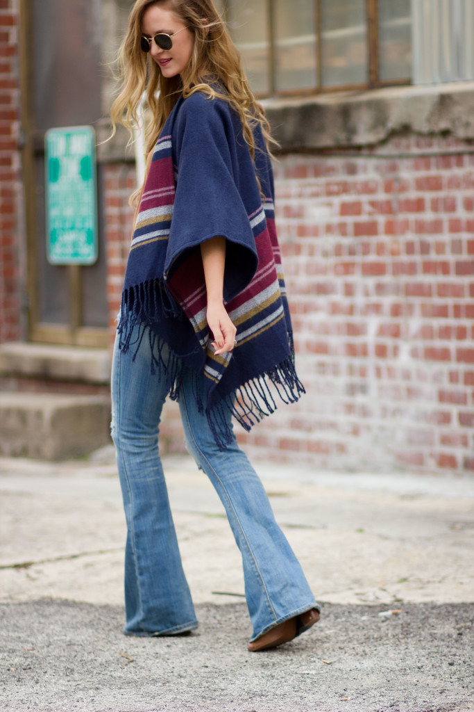 Hollister fringe poncho, American Eagle flared jeans, and round Ray Ban sunglasses