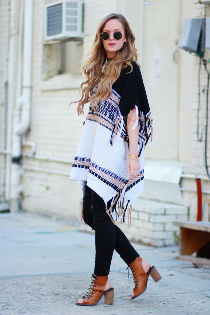 Florida fashion blogger styles fringe boho poncho, DSTLD black distressed jeans, metal round ray ban sunglasses