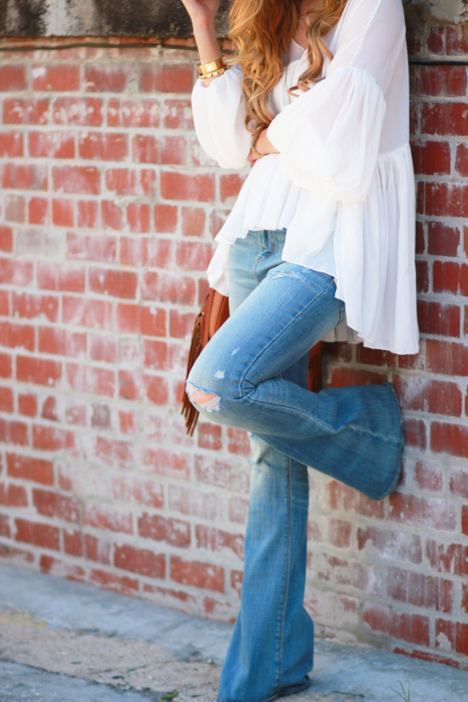Orlando Florida fashion blog styles Chicwish flowy blouse, American Eagle flared jeans, and Sancia fringe bag for a causal spring outfit