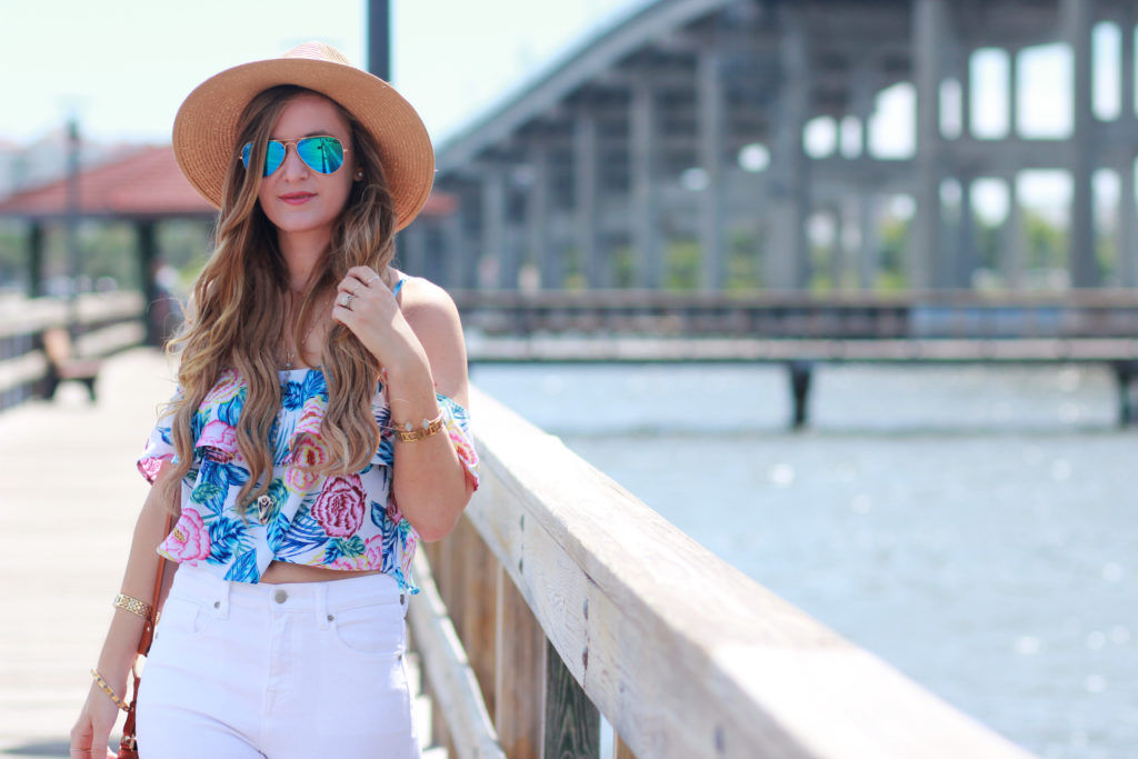Orlando Florida fashion blog styles H&M floral crop top with Forever 21 white flared jeans, Sancia fringe bag, and Ray Ban mirrored sunglasses.