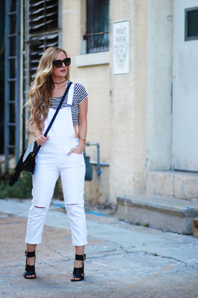 Shannon Jenkins of Upbeat Soles styles a fall transition outfit with Forever 21 white overalls, striped crop top, and Valley Eyewear sunglasses