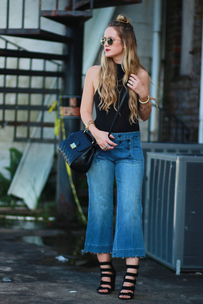 Shannon Jenkins of Upbeat Soles styles a fall transition outfit with Michael Kors culottes, mockneck bodysuit, Ray Ban Icons, and leather Vera Bradley bag