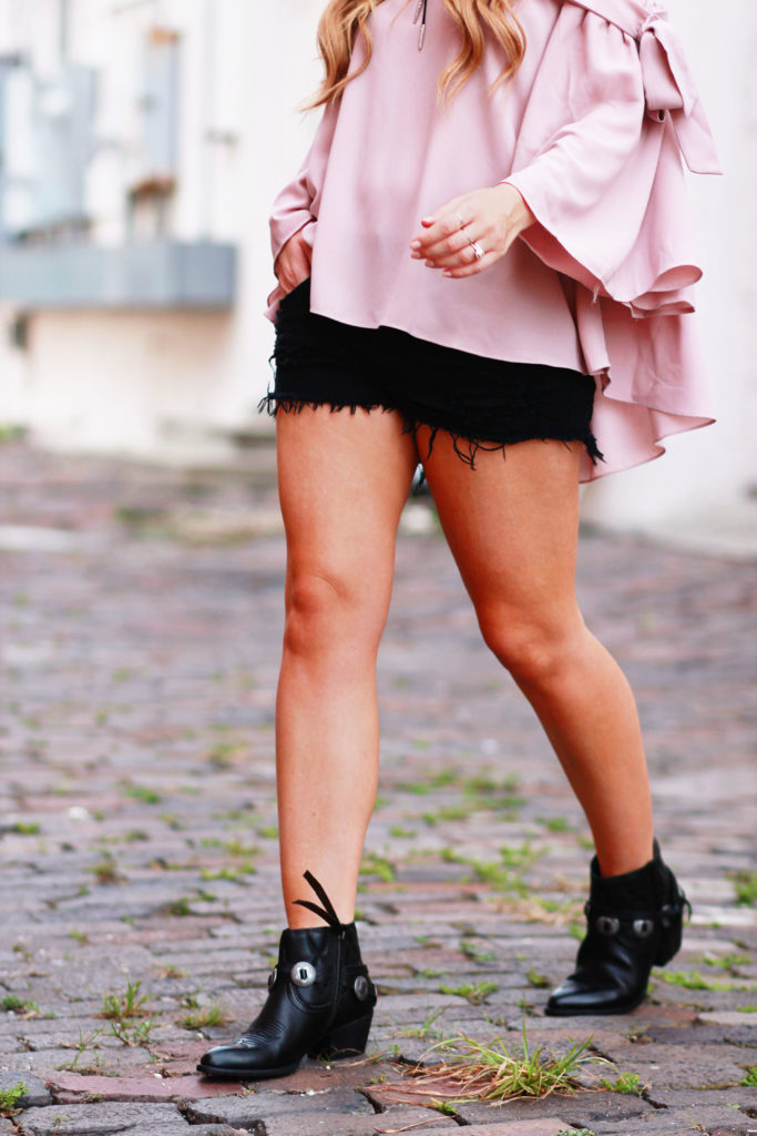 Shannon Jenkins of Upbeat Soles styles a boho fall transition outfit with a flowy Chicwish top, American Eagle denim shorts, and Dolce Vita Skye booties