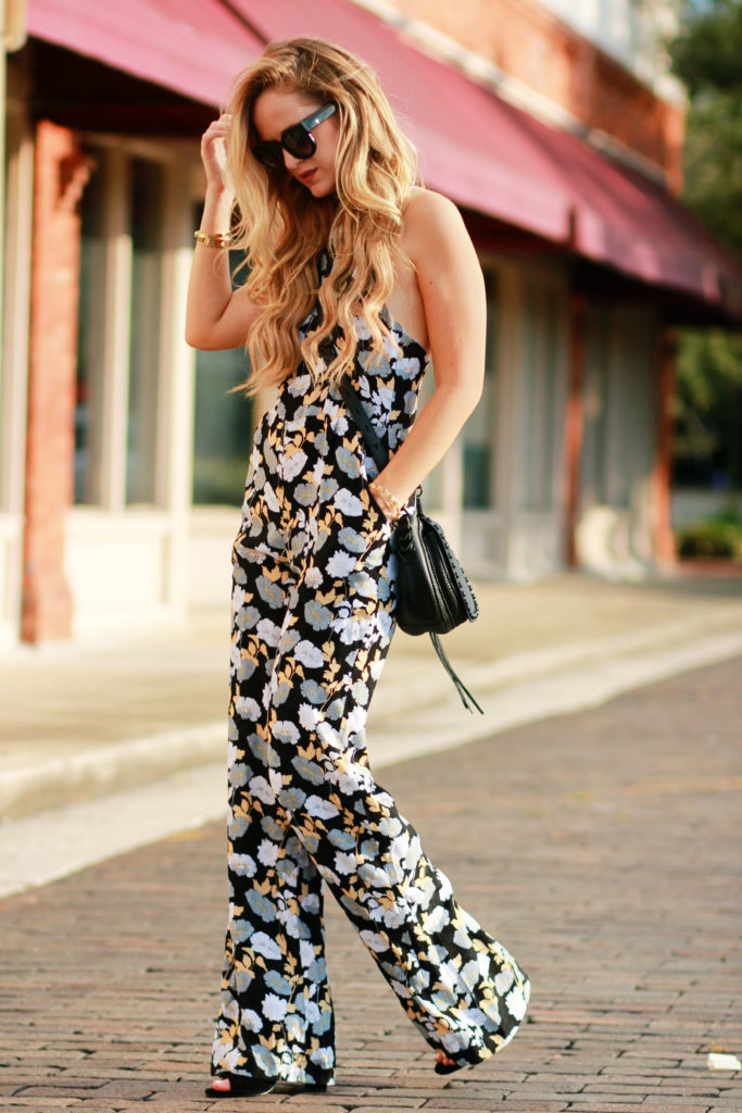 Shannon Jenkins of Upbeat Soles styles a fall floral jumpsuit from Shore with Kendall and Kylie strappy heels, and Rebecca Minkoff saddle bag