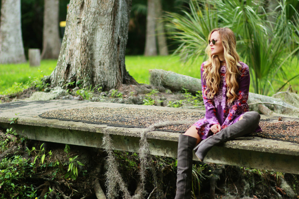 Shannon Jenkins of Upbeat Soles styles a fall transition outfit with Free People floral backless dress, grey suede over the knee boots and Ray Ban Icons