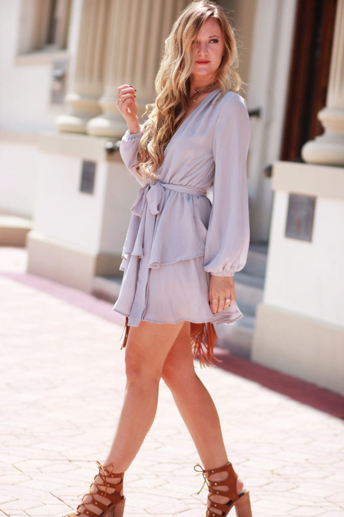 Shannon Jenkins of Upbeat Soles styles a sexy date night outfit with Lioness grey ruffle dress, Dolce Vita lace up sandals, and Sancia crossbody bag