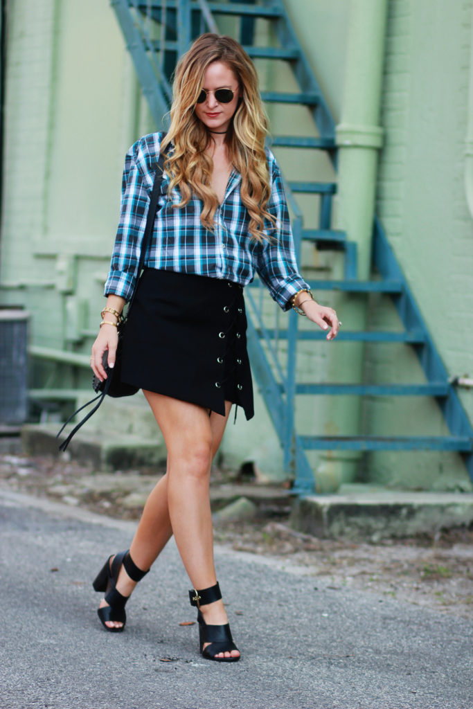 Shannon Jenkins of Upbeat Soles styles a fall transition outfit with a boyfriend plaid shirt, lace up skirt, black block heels, adn Rebecca Minkoff stud bag