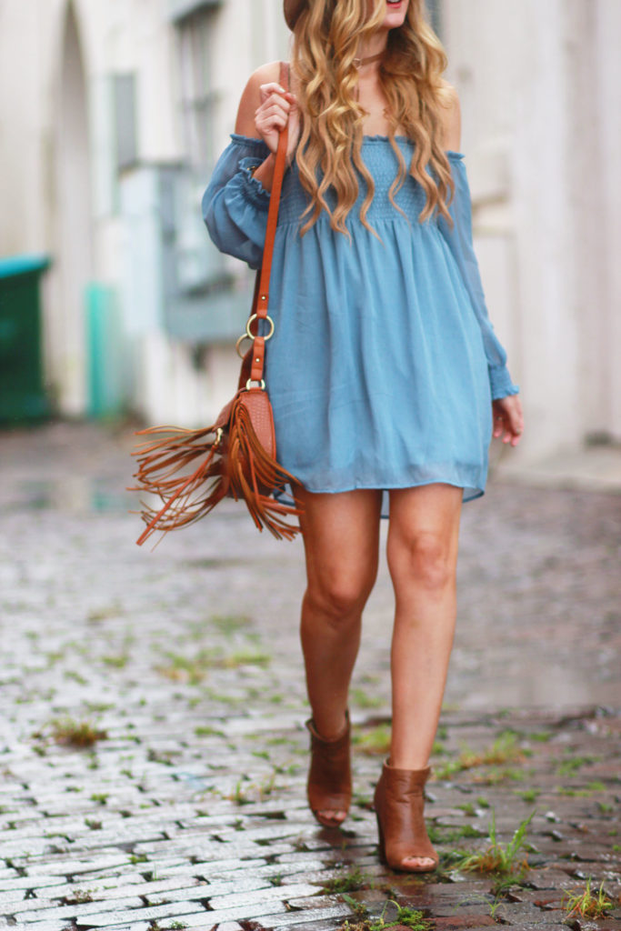 Shannon Jenkins of Upbeat Soles styles a fall transition outfit with Chicwish off the shoulder blue dress, tan peep toe booties, and Sancia fringe crossbody