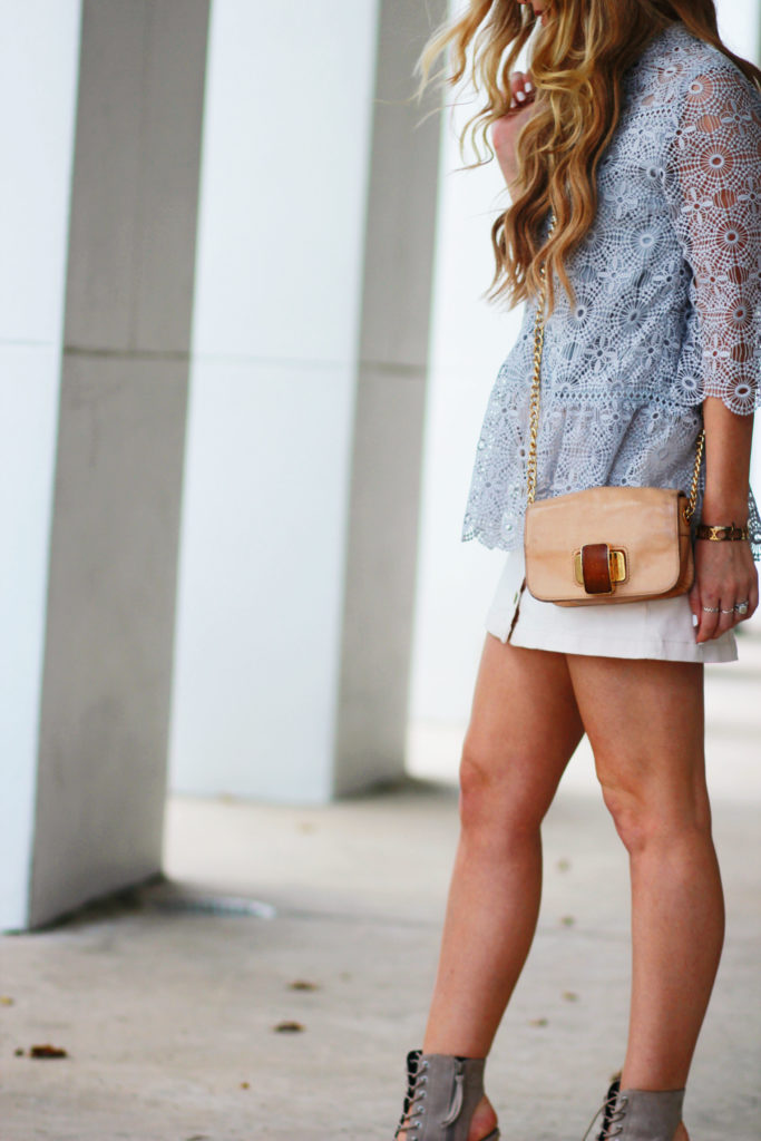 Shannon Jenkins of Upbeat Soles styles a fall transition outfit with a Chicwish grey lace top, denim button up skirt, and Rebecca Minkoff lace up wedges