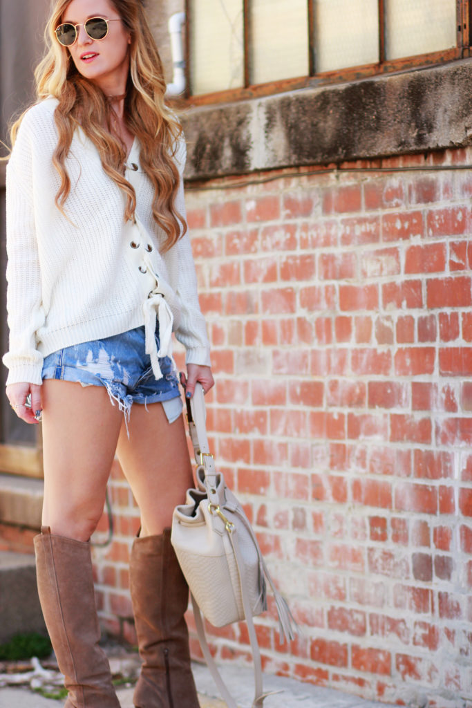 Shannon Jenkins of Upbeat Soles styles a casual fall transition outfit with a lace up sweater, distressed denim shorts, and GiGi New York bucket bag