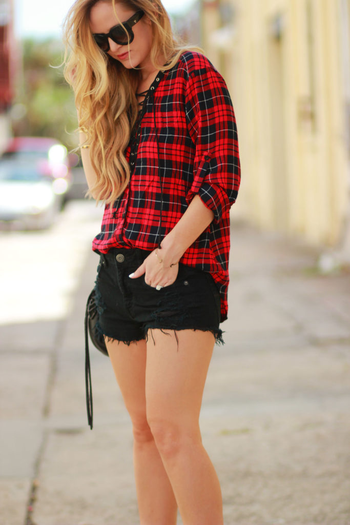Shannon Jenkins of Upbeat Soles styles a fall transition outfit with a Shein lace up plaid shirt, black jean shorts, and black Sole Society booties