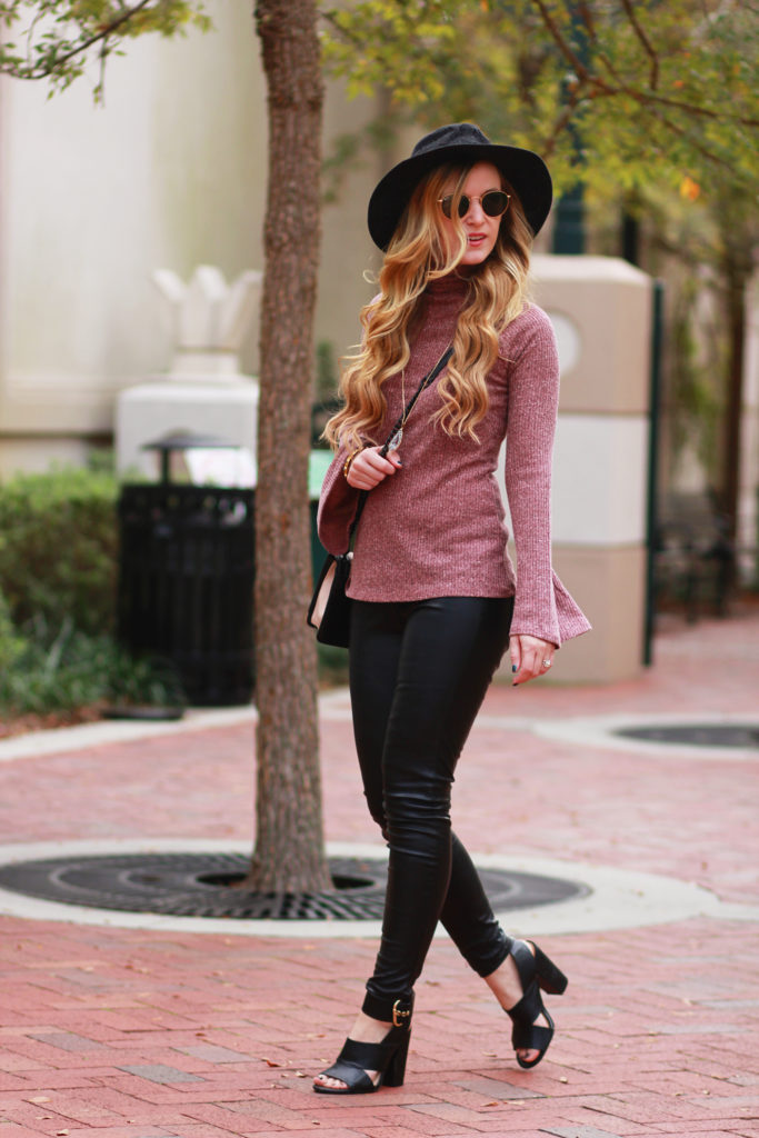 Shannon Jenkins of Upbeat Soles styles a casual fall outfit with Target bell sleeve sweater, faux leather pants, and Love Rebecca Minkoff bag