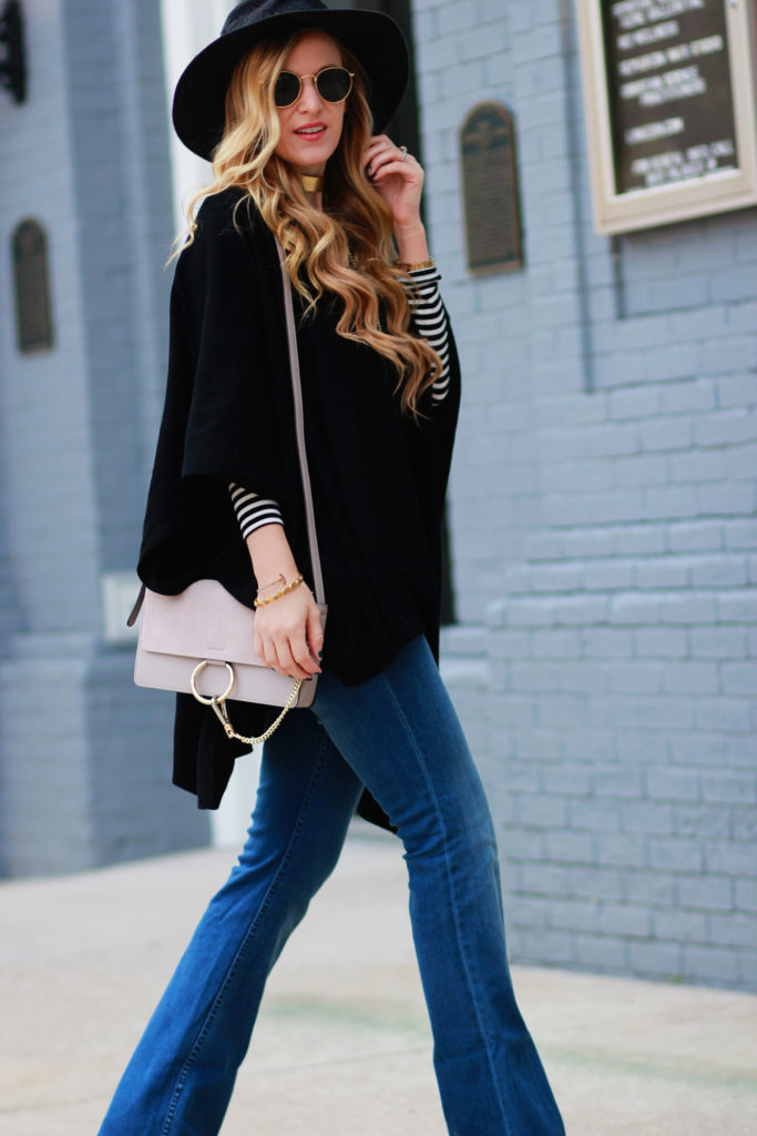 Shannon Jenkins of Upbeat Soles styles a casual fall outfit with cashmere Tommy Bahama poncho layered with a striped shirt, flared jeans, and round Ray Bans