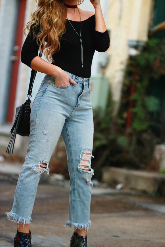 Shannon Jenkins of Upbeat Soles styles an edgy winter outfit with Express bodysuit, distressed mom jeans, Sam Edelman booties, and velvet chocker