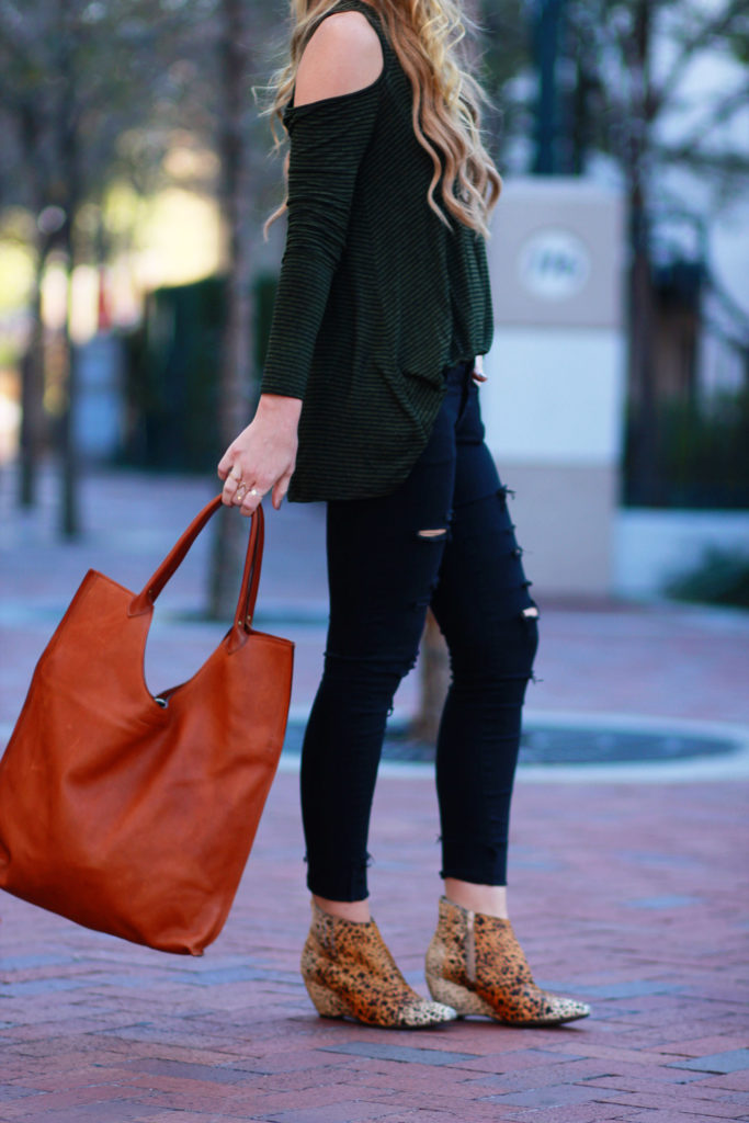Shannon Jenkins of Upbeat Soles styles a casual fall outfit with Lush cut out shoulder top, DSTLD jeans, Matisse Nugent booties, and Pennyroyal bag