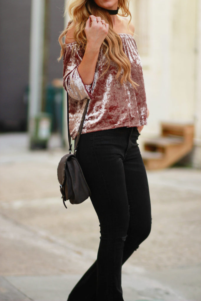 Shannon Jenkins of Upbeat Soles styles an edgy fall outfit with American Eagle velvet off the shoulder top, black flared jeans, Rebecca Minkoff biker bag