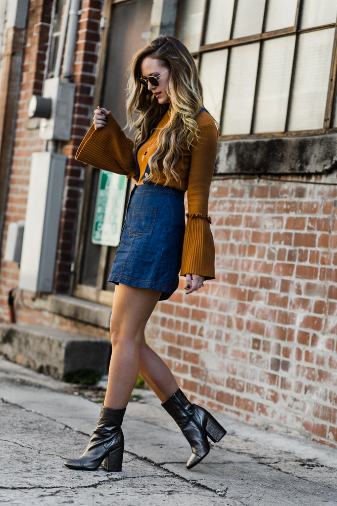 Shannon Jenkins of Upbeat Soles styles a 70s inspired outfit with Hollister denim overalls, Chicwish bell sleeve sweater, and Kendall + Kylie silver booties