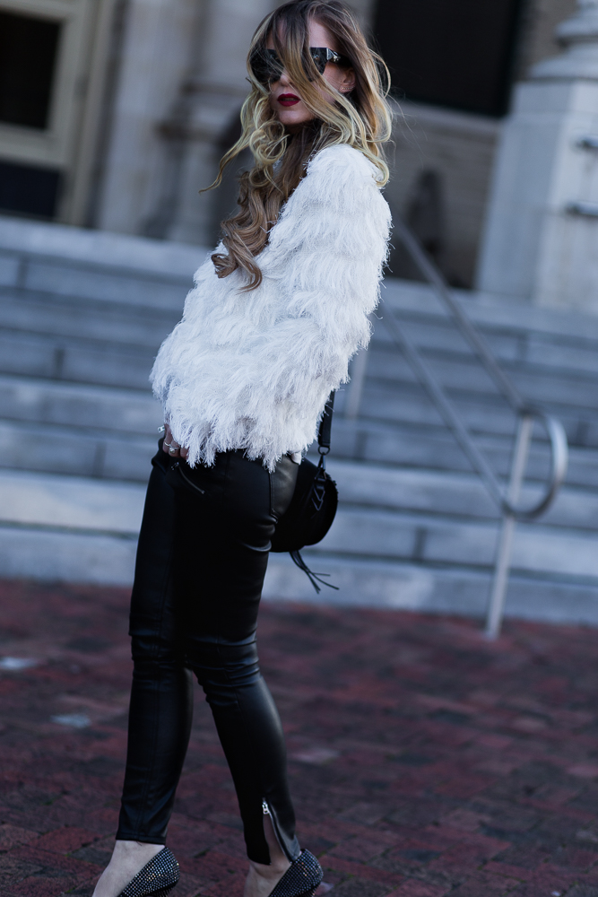 Shannon Jenkins of Upbeat Soles styles edgy winter outfit styled with faux fur top, H&M leather pants, Rebecca Minkoff saddle bag, and Valley Eyewear