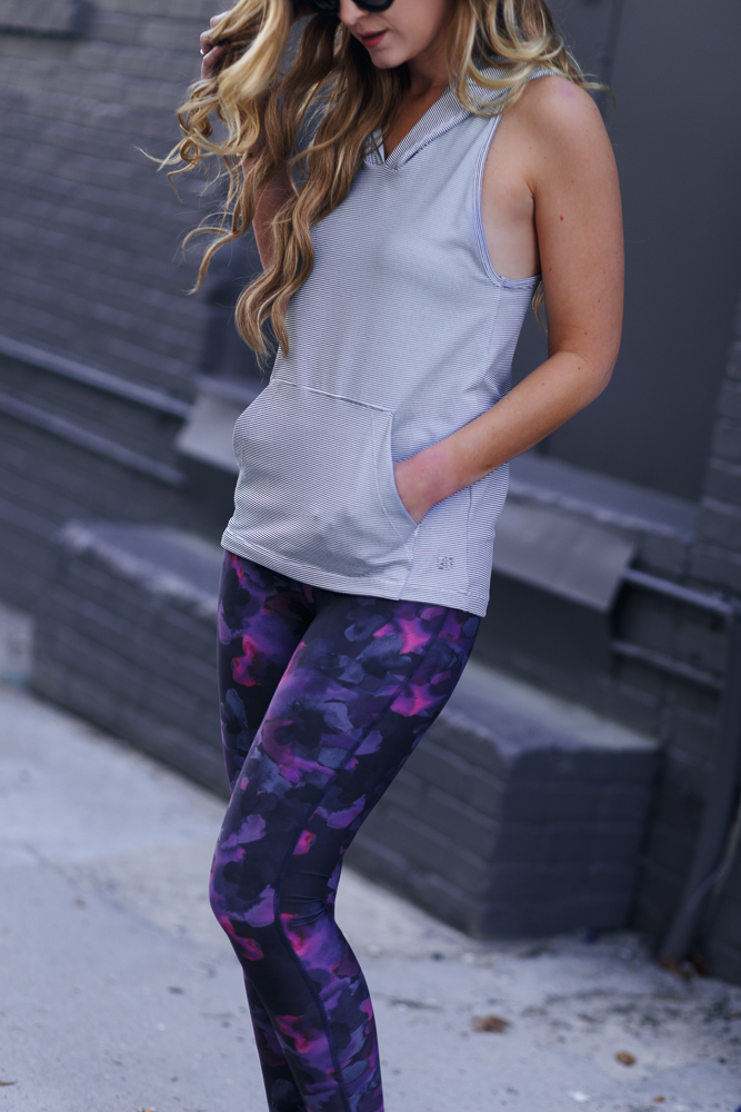 Shannon Jenkins of Upbeat Soles styles a cute workout outfit with Albion Fit sleeveless hoodie, pattern leggings, and Nike Juvenate sneakers