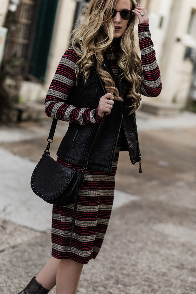 Shannon Jenkins of Upbeat Soles styles edgy winter outfit with Chelsea & Violet striped midi dress, leather vest, and metallic booties