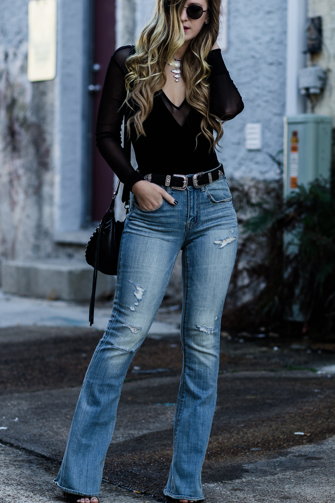 Shannon Jenkins of Upbeat Soles styles edgy winter outfit with BCBGeneration velvet bodysuit, American Eagle flared jeans, and Kendra Scott Morris necklace