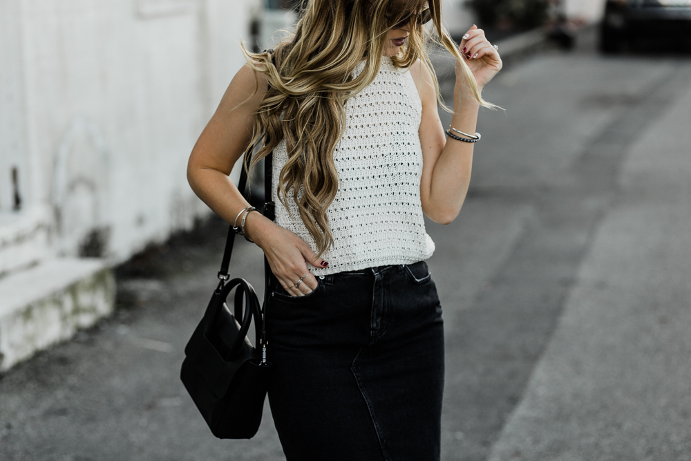 Shannon Jenkins of Upbeat Soles shows how to style a a black denim skirt from H&M, velvet booties, crochet crop top, and back round sunglasses