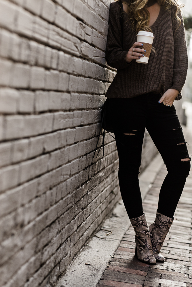 Shannon Jenkins of Upbeat Soles styles edgy winter outfit with brown choker sweater, DSTLD ripped jeans, and Target snakeskin booties