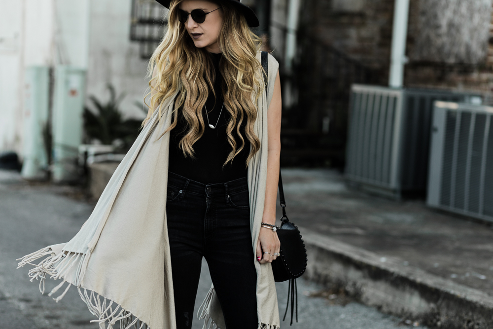 Shannon Jenkins of Upbeat Soles a black flared jeans outfit with fringe cardigan, Rebecca Minkoff saddle bag, Free People hat, and black round sunglasses