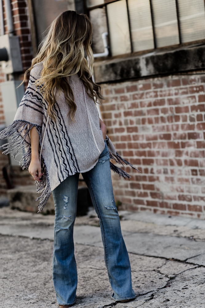 Shannon Jenkins of Upbeat Soles shows how to style flared jeans and a fringe poncho for a spring boho outfit with round Ray Ban Icon sunglasses