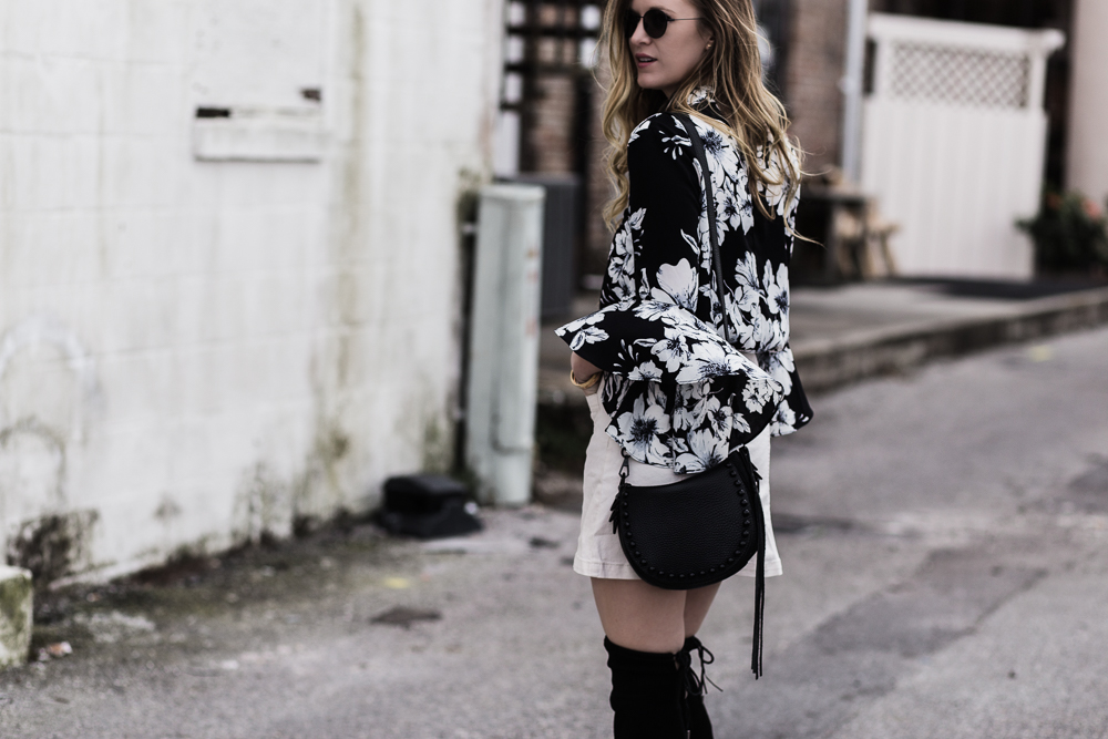Shannon Jenkins of Upbeat Soles styles black and white spring transition outfit with Gianni Bini bell sleeve floral top, H&M button up skirt, and OTK boots