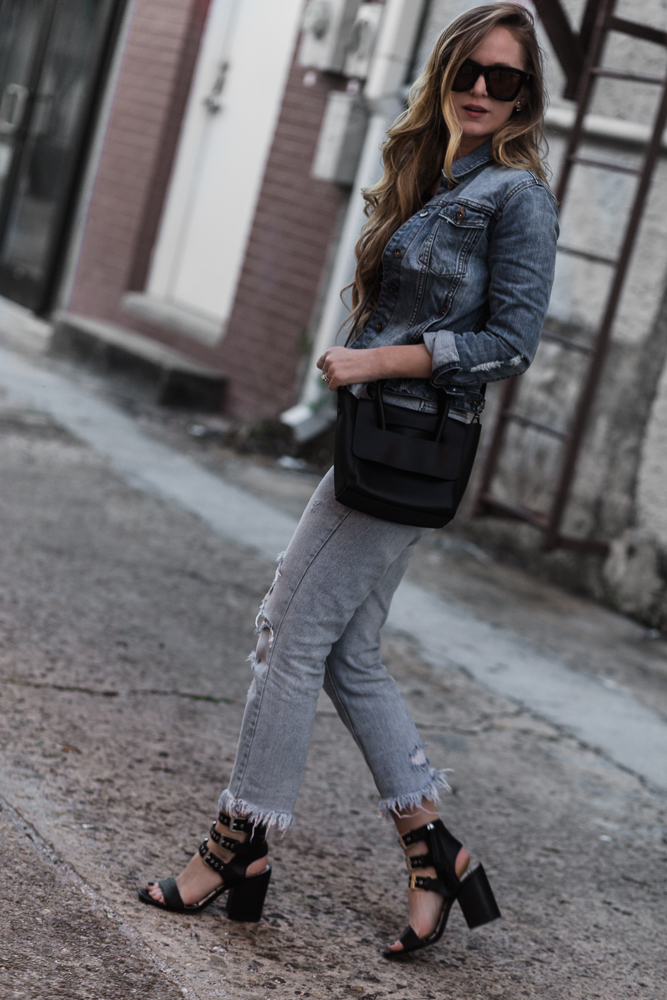 Shannon Jenkins of Upbeat Soles styles denim on denim outfit with DSTLD denim jacket, striped lace up top, distressed mom jeans, Dolce Vita block sandals