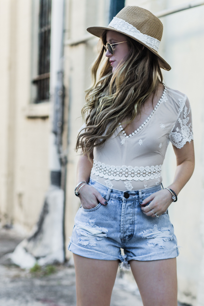 Shannon of Upbeat Soles shows how to style a lace bodysuit for spring with high waisted denim shorts, Jeffrey Campbell Cordia booties, and round Ray Bans