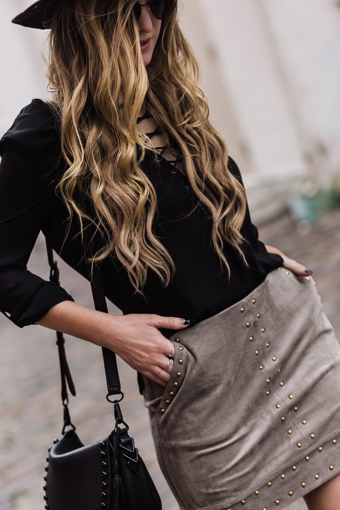 Shannon Jenkins of Upbeat Soles styles a spring transition outfit with black lace up shirt, Gianni Bini studded suede skirt, and black fringe booties