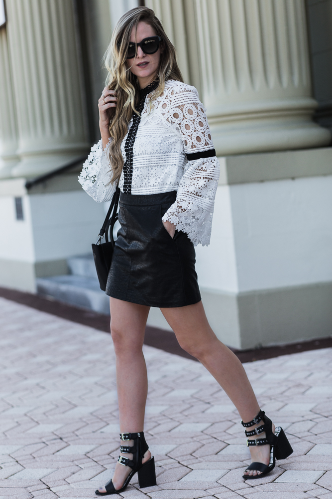 Shannon Jenkins of Upbeat Soles styles an easy Friday night outfit with black and white lace bell sleeve top, leather mini skirt, and block heel sandals