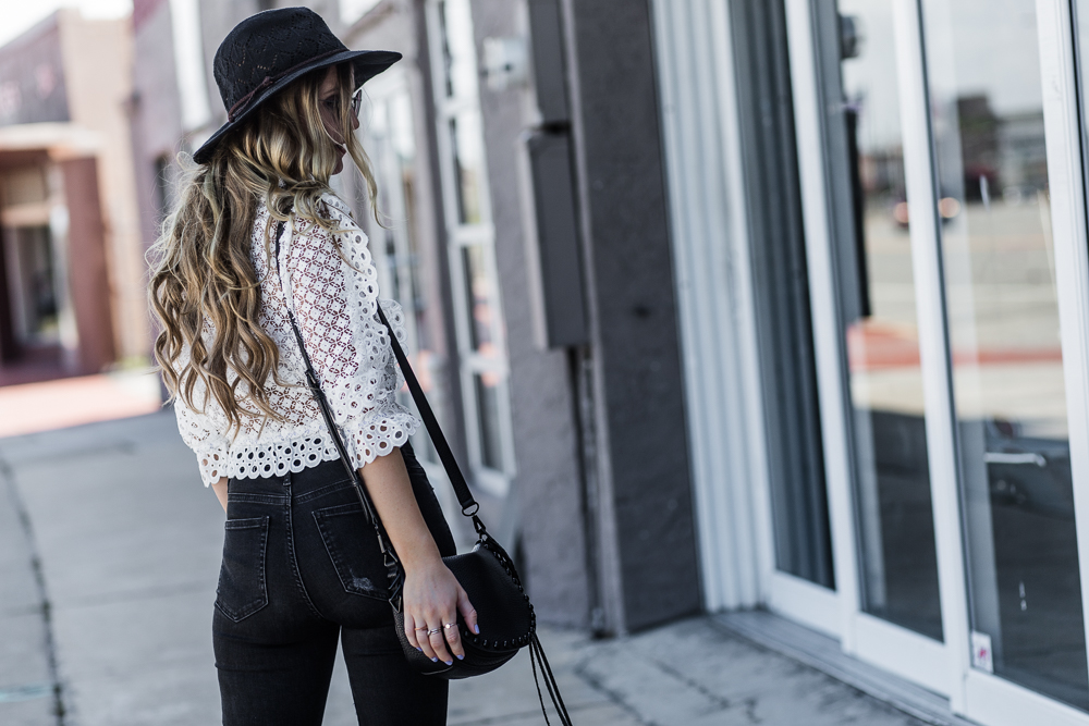 Shannon Jenkins of Upbeat Soles styles spring boho outfit with laced crop top, black flared jeans, Free People hat, and does a Skinit phone case review