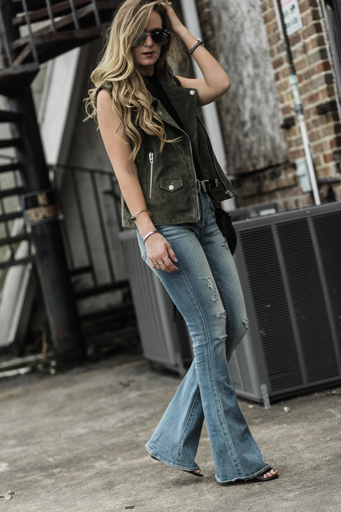 Shannon Jenkins of Upbeat Soles styles and edgy outfit for spring with suede BlankNYC moto vest, AE flared jeans, and Quay Playa sunglasses