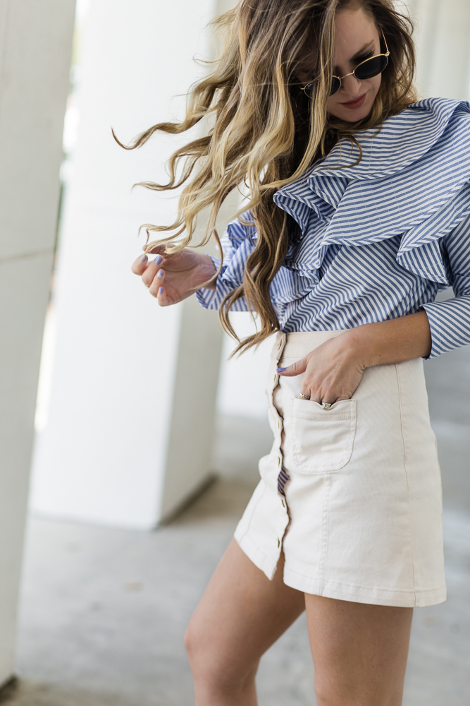 Shannon Jenkins of Upbeat Soles styles a cute vacation outfit with a one shoulder stripe and ruffle top with white button up skirt, Dolce Vita studded heels