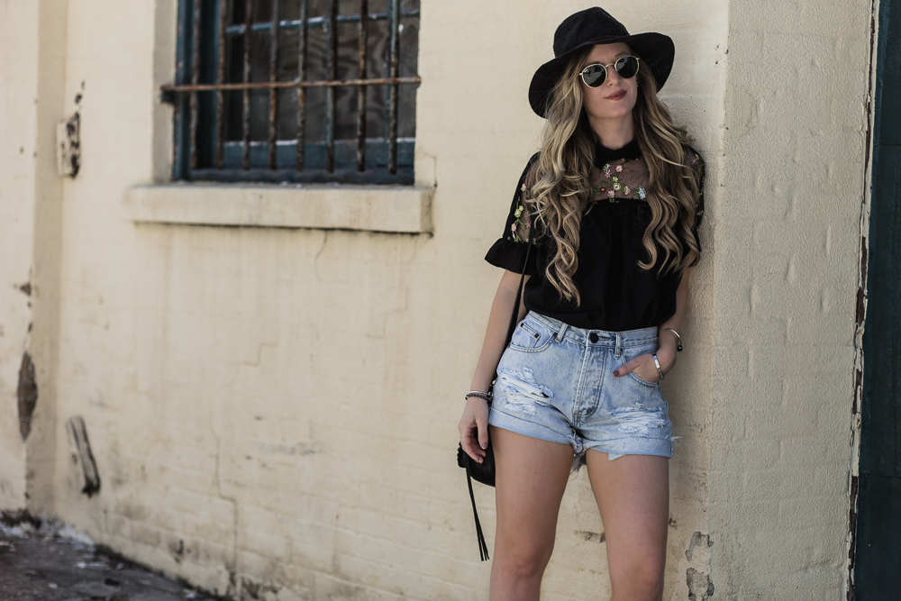 Shannon Jenkins of Upbeat Soles styles a spring brunch outfit with sheer and embroidered top, Tobi distressed high waisted shorts, and Rebecca Minkoff bag
