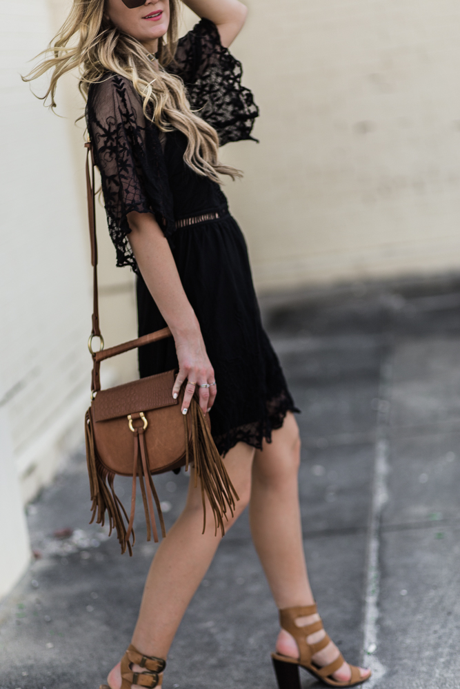 Shannon Jenkins of Upbeat Soles styles a dressy boho outfit with black lace dress, buckle block heels, and fringe crossbody bag
