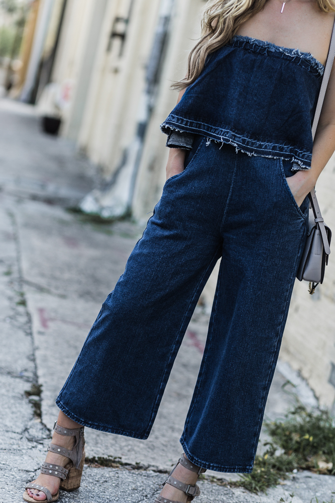 Shannon Jenkins of Upbeat Soles styles a spring date night outfit with JOA denim jumpsuit, Dolce Vita block heel sandals, and Chloe Faye dupe
