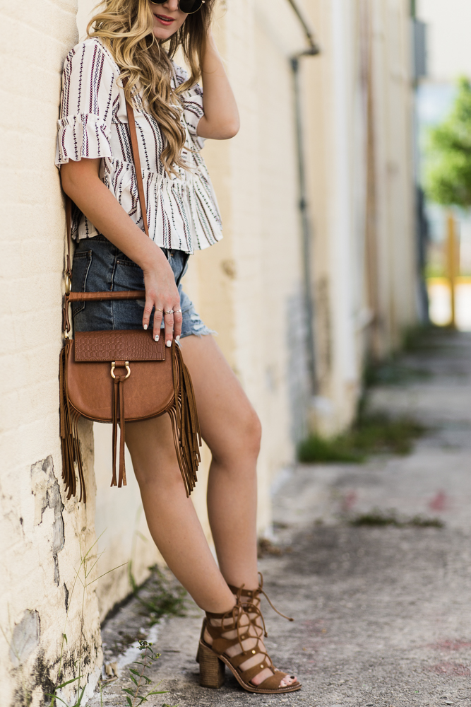 Shannon Jenkins of Upbeat Soles styles a cute casual spring outfit with striped lace up top, distressed denim shorts, and Dolce Vita lace up sandals