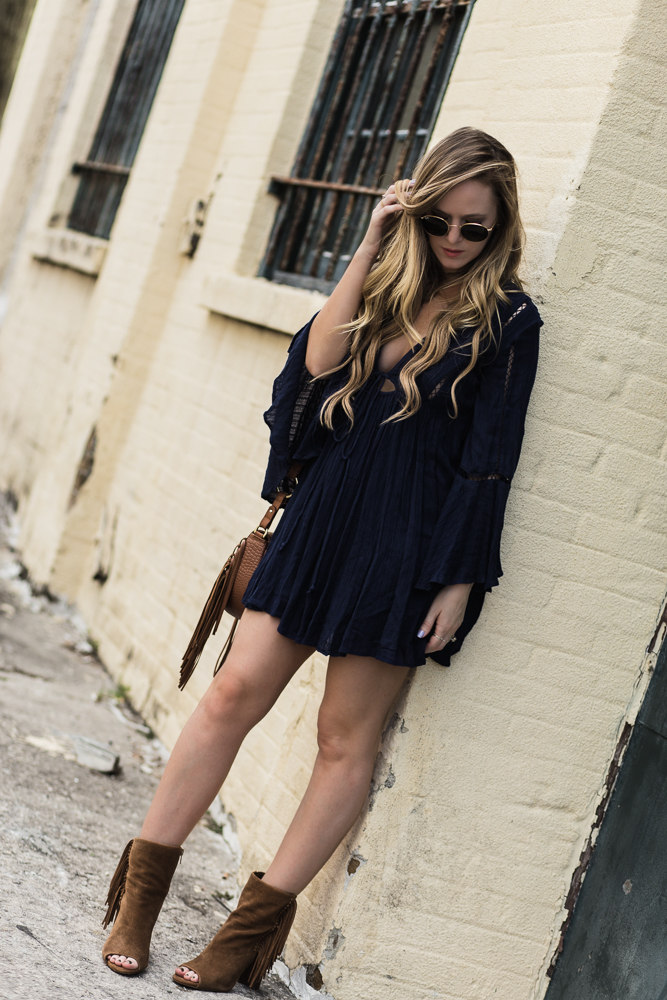 Shannon Jenkins of Upbeat Soles styles a boho spring outfit with navy Roman Free People dress, Dolce Vita fringe booties, and round Ray Ban sunglasses