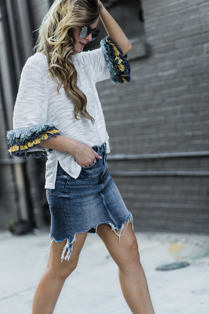 Shannon Jenkins of Upbeat Soles styles sporty chic outfit with Shein fringe top, distressed denim skirt, adidas Neo sneakers, and Quay sunglasses