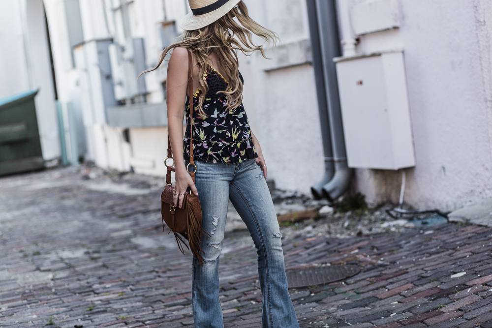 Shannon Jenkins of Upbeat Soles styles a casual boho spring outfit with Chelsea & Violet crochet top, American Eagle flared jeans, and round Ray Ban sunnies
