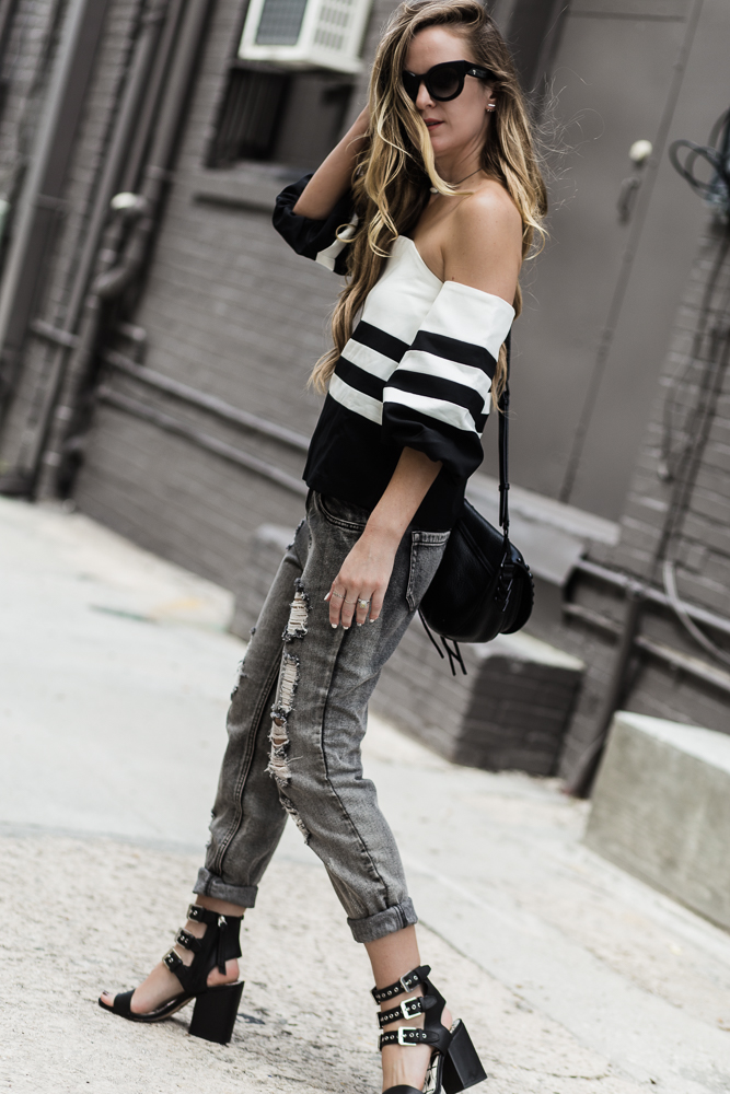 Shannon Jenkins of Upbeat Sole styles an edgy summer outfit with black and white off the shoulder top, grey boyfriend jeans and Dolce Vita black block heels