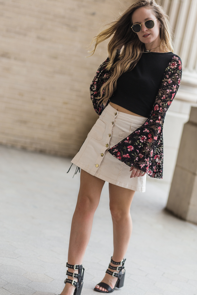 Shannon Jenkins of Upbeat Soles styles a summer date night outfit with a lace bell sleeve crop top, white denim skirt, and Dolce Vita buckle sandals