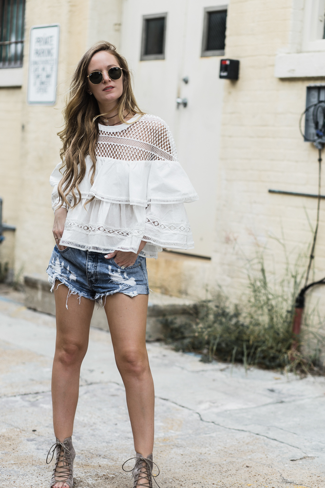 Shannon Jenkins of Upbeat Soles styles summer boho outfit with lace ruffle top, one teaspoon bandit shorts, lace up Jeffrey Campbell wedges, and Rox Jewelry