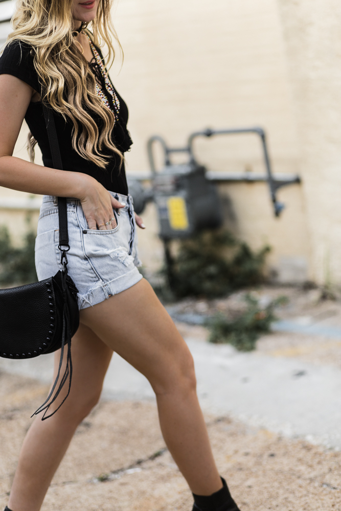 Shannon Jenkins of Upbeat Soles styles an edgy summer outfit with lace up black bodysuit, high waisted distressed shorts, and black ankle booties