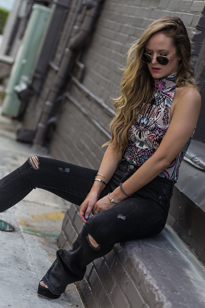 Shannon Jenkins of Upbeat Soles styles a easy weekend boho outfit with patterned bodysuit, black high waisted flared jeans, and round Ray Ban sunglasses
